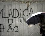 """Žena prochází kolem grafitu """"S Mladićem do Haagu"""""""